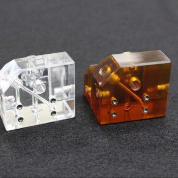 Precision Machined Ultem Manifold Next to a Precision Machined Acrylic Manifold