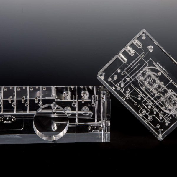 Precision Machined Acrylic Manifold Next to a Clear Diffusion Bonded Acrylic Fluidic Manifold
