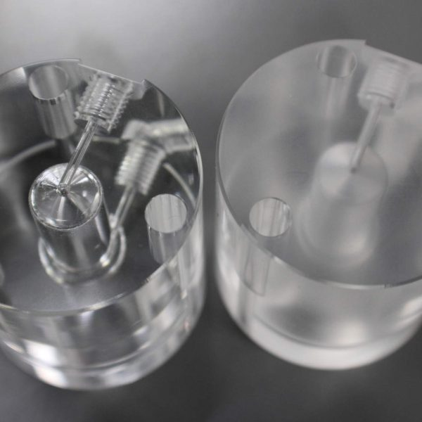 Vapor Polished Machined Plastic Manifold Next to the Same Plastic Part that is not Vapor Polished